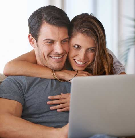 brunette man on laptop, brunette woman behind him, leaning over with arms around him