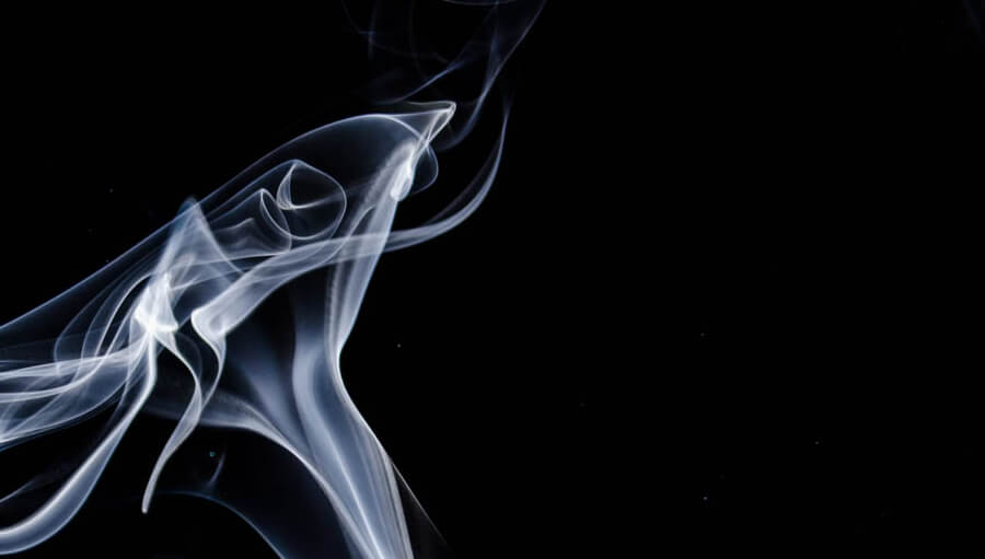 Wisps of tobacco smoke against a black background