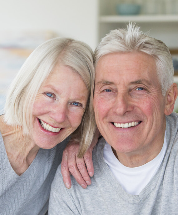 elderly couple with dental implants smiling