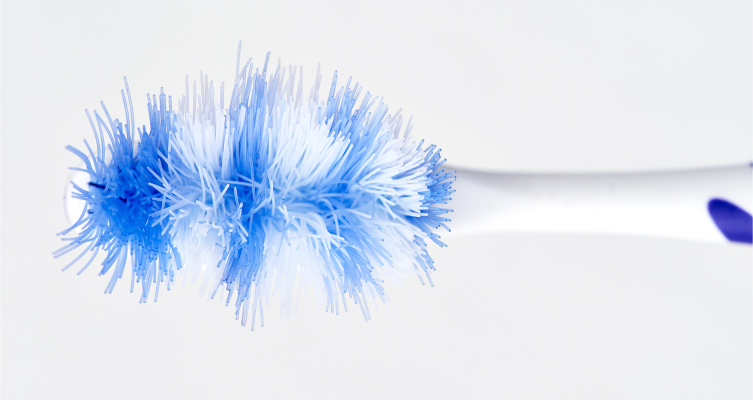Overhead view of a blue and white toothbrush with frayed and smashed bristles