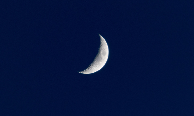 White crescent moon against a dark navy blue midnight sky