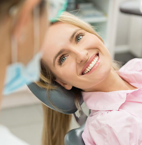 smiling, blonde woman lying in dental chair, speaking with her hygienist