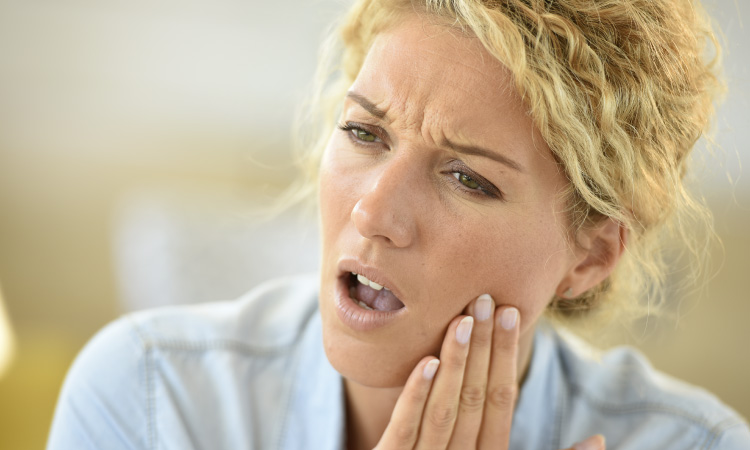 Closeup of a blonde woman touching her cheek due to painful dry socket