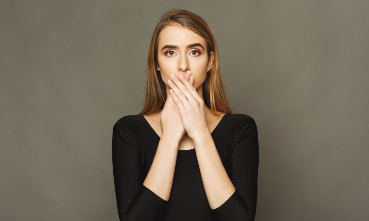 Blonde woman wearing a black shirt covers her mouth with her hands because she is embarrassed about her halitosis