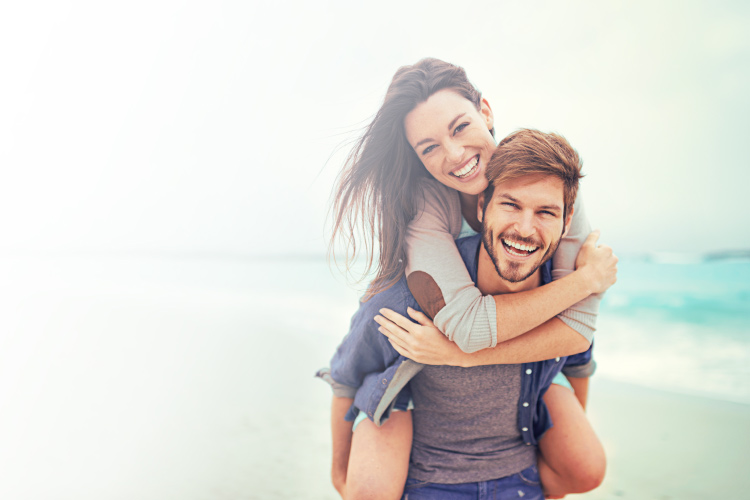 Brunette man gives a piggy back ride to a brunette woman while smiling on a beach