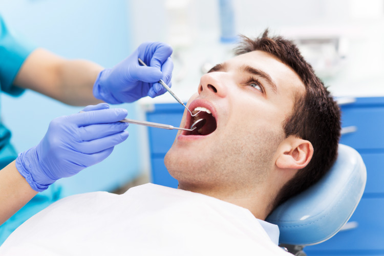 Brunette man sits in a dental chair with a white bib as a hygienist examines his mouth with dental tools