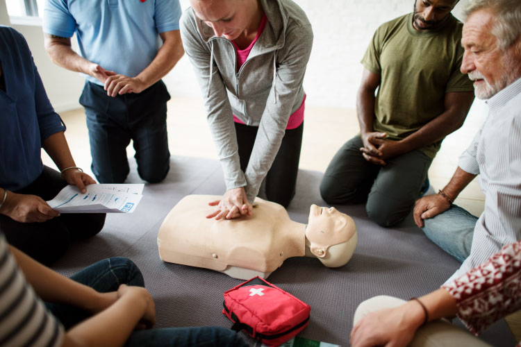 A group of people learn and practice CPR with an AED on a dummy torso