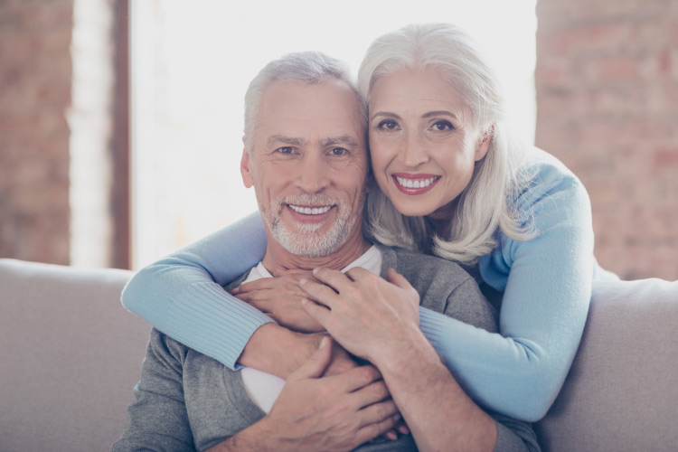 A white-haired husband and wife smile with dentures as they embrace on the couch