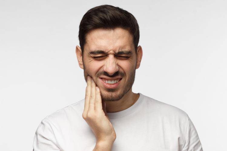 Dark-haired man cringing in pain and touching his cheek due to a toothache
