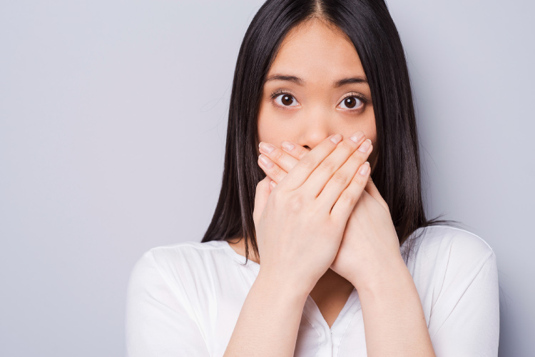 Dark-haired woman with bad breath covers her mouth with her hands in embarrassment