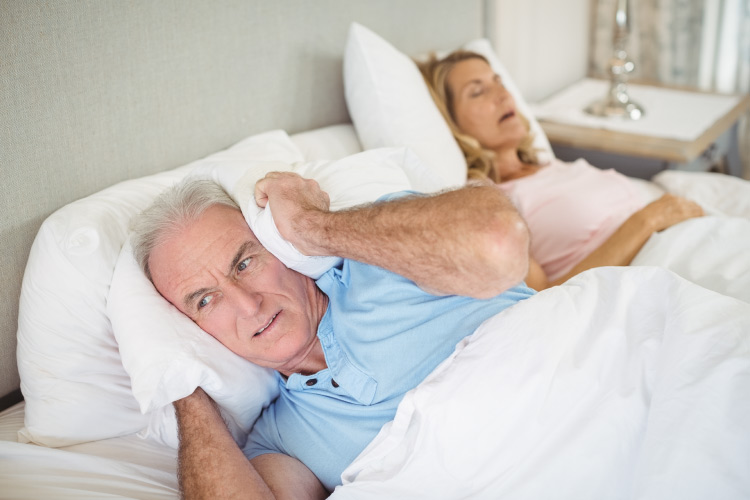 An older man in bed holds a pillow over his ear while his wife with sleep apnea snores loudly next to him
