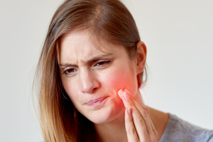 Blonde girl with her hand to her cheek and a pained facial expression due to a toothache.
