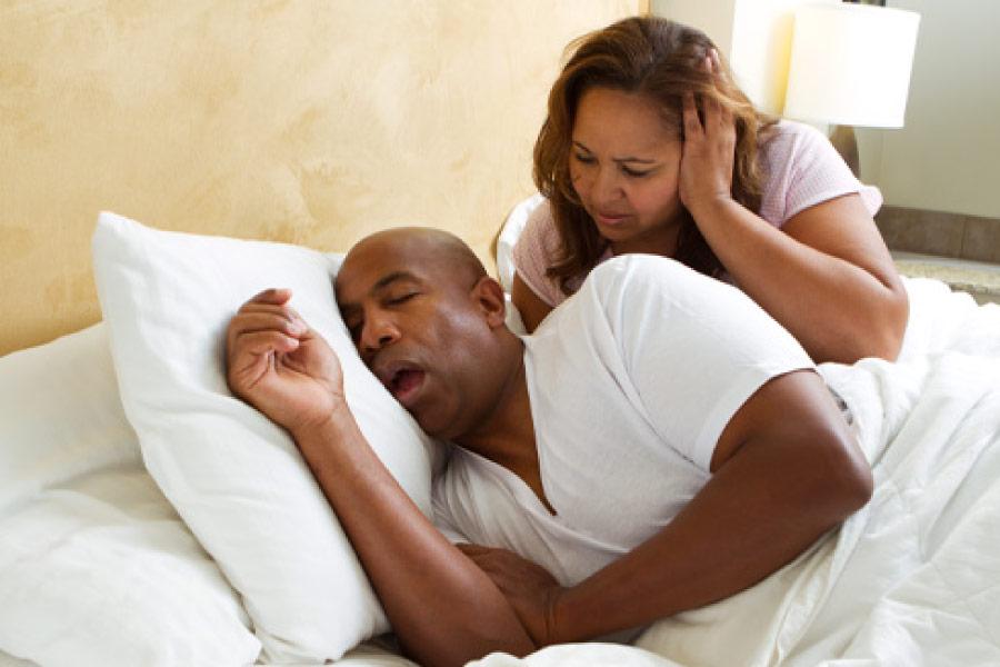Snoring man with sleep apnea keeps his wife from sleeping.