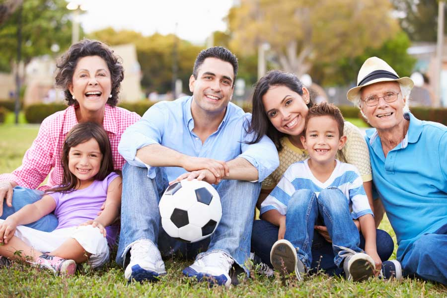 Multigenerational hispanic family sitting at the park with a soccer ball.